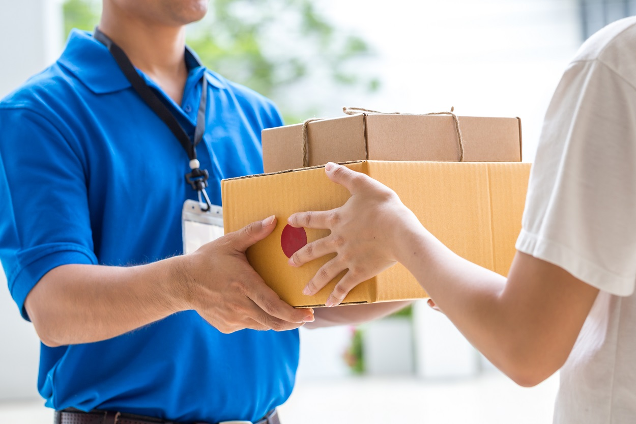 Woman hand accepting a delivery of boxes from courier service